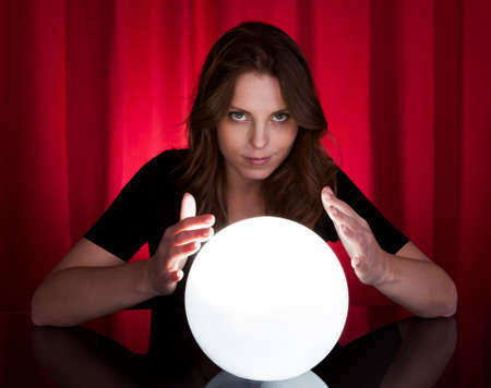 Beautiful young fortuneteller holding her hands around a glowing ball as she foretells the future and what it holds