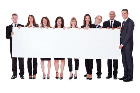 Group of stylish professional business people standing in a line holding up a long blank banner for your advertising or textの写真素材