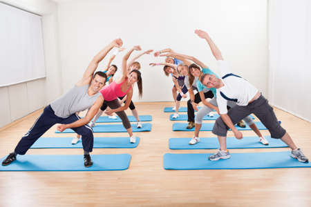 Large group of diverse people doing aerobics exercises in a gym standing on blue mats