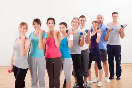 Aerobics class of diverse men and women of different ages working out in a gym with dumbbells flexing their arm muscles