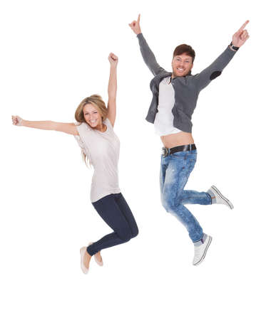 Jubilant young man and woman leaping high in the air for joy with their arms raised isolated on white