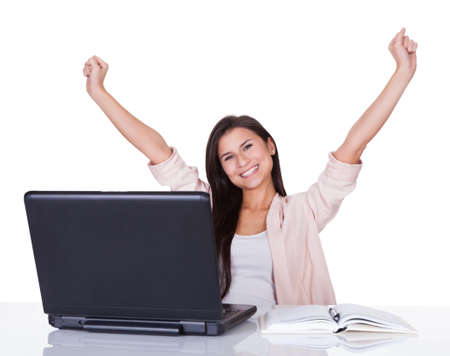 Happy beautiful vivacious female office worker or businesswoman rejoicing raising her hands high in the air