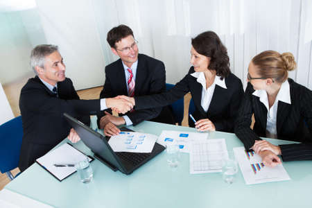 Business colleagues seated around a table in a meeting congratulating one another by shaking handsの写真素材