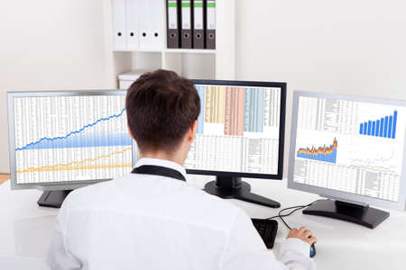 Photo pour Over the shoulder view of the computer screens of a stock broker trading in a bull market showing ascending graphs - image libre de droit
