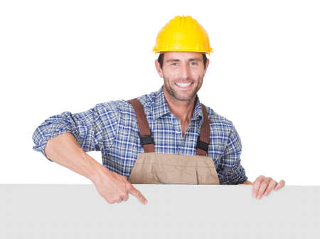 Portrait of happy construction worker presenting empty banner. Isolated on white