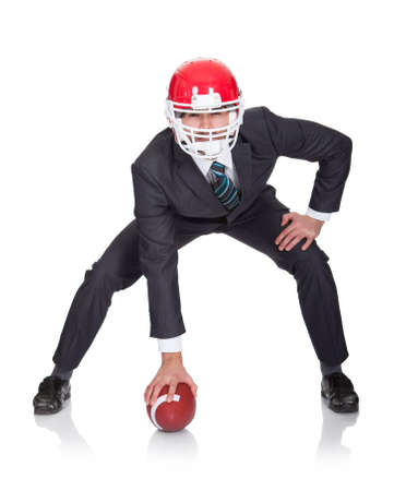 Competitive businessman playing american football. Isolated on white