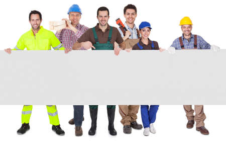 Group of workers presenting empty banner. Isolated on white