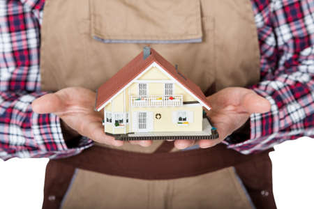 Construction worker holding house model. Isolated on white background