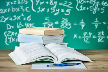 School textbooks on a desk in front of blackboard