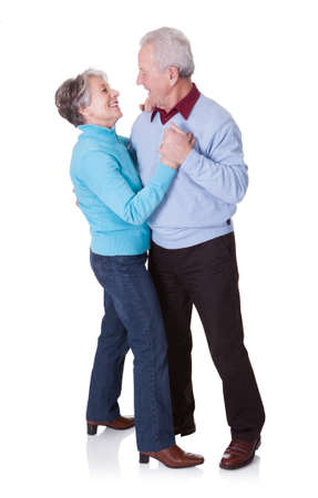 Portrait Of Senior Couple Dancing On White Backgroundの写真素材