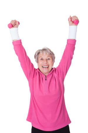 Portrait Of A Senior Woman Exercising On White Background