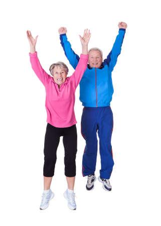 Portrait Of Senior Couple Jumping In Joy Over White Background