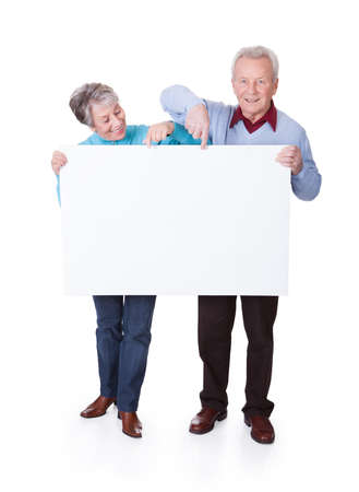 Happy Senior Couple Holding Blank Placard On White Backgroundの写真素材