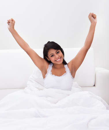 Young Happy Woman Stretching Her Arms On Bed