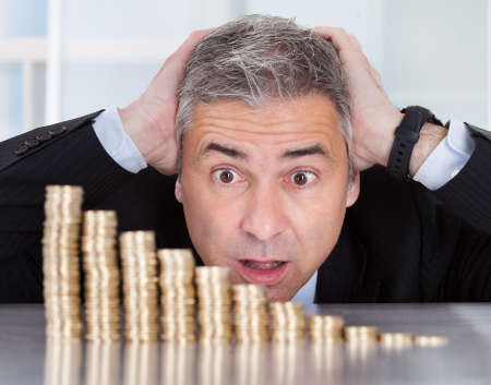 Shocked Mature Businessman Looking At Descending Stack Of Coins