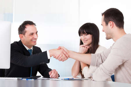 Photo pour Consultant Shaking Hands With A Man In Office - image libre de droit