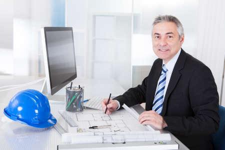 Photo pour Portrait Of Mature Architect Male With Blueprint In The Office - image libre de droit