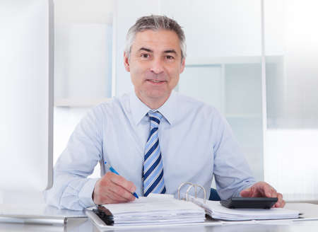 Portrait Of Mature Businessman Calculating Finance At Office