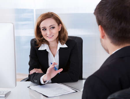 Two businesspeople talking with each other at office