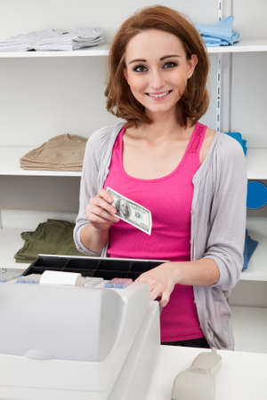Happy Young Female Cashier With Cash Register At Cash Counter