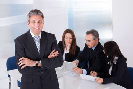 Foto de Happy Mature Businessman Standing In Front Of Colleagues In Office - Imagen libre de derechos