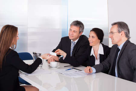 Businesswoman Offering Business Card To Colleague In Office