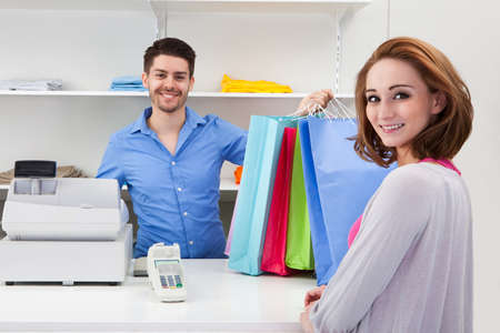 Happy Male Cashier Handing Over Shopping Bag To Customer
