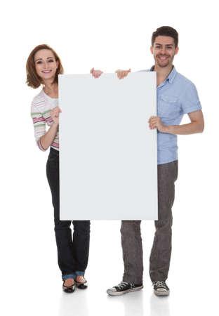Photo pour Young Happy Couple Holding Placard Over White Background - image libre de droit