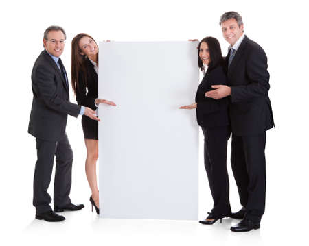 Happy Business People Showing Placard Over White Backgroundの写真素材