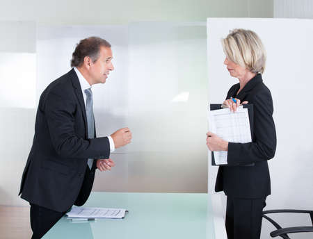 Mature Businessman And Businesswoman Looking At Each Other With Angry