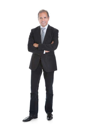 Portrait Of A Well Dressed Businessman Standing With Arms Crossed
