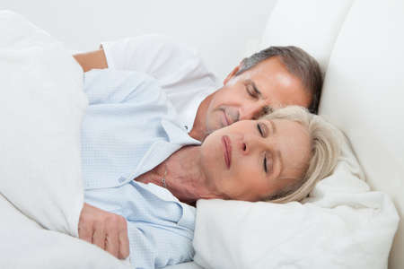 Portrait Of Happy Senior Couple Sleeping Together In Bed