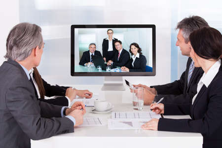 Photo for Group Of Businesspeople In Video Conference At Business Meeting - Royalty Free Image
