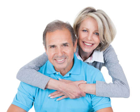 Woman Embracing Mature Man From Behind Sitting On Pilates Ballの写真素材