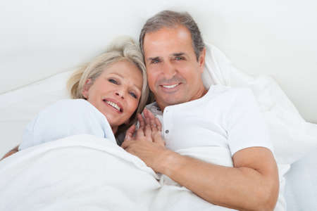 Portrait Of Happy Senior Couple On Sleeping Bed Together