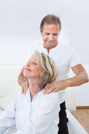 Mature Man Massaging Woman's Shoulder In Bed