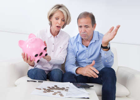 Portrait Of Shocked Couple Holding Piggybank At Home