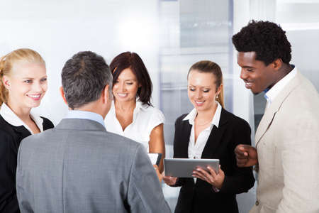 Group Of Happy Multiracial Businesspeople Looking At Digital Tablet