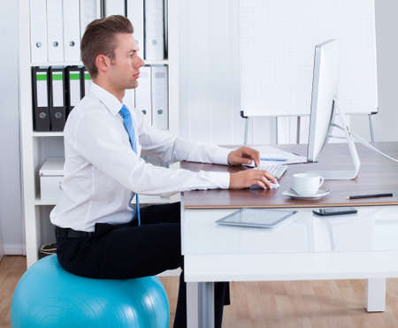 Businessman Sitting Comfortably On Pilates Ball And Using Computer In Office