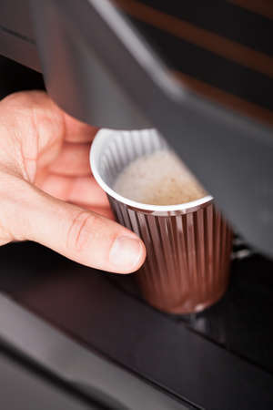 Coffee maker pouring hot espresso coffee in a glass