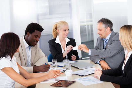Businesspeople In A Meeting Exchanging Visiting Card