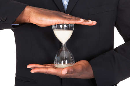 Close-up Of African Businessman Holding Hourglass In Hands