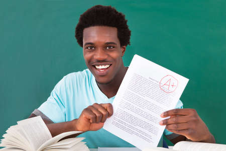 Happy African Male Student Showing A Paper With Perfect Grade A Plus In Classroom