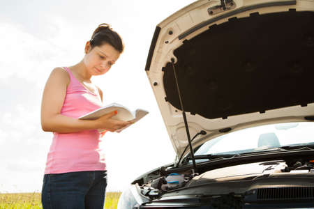 Young Woman Reading Book On Front Of Car With Open Hood