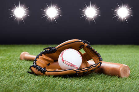 Baseball Glove With Baseball And Bat Lying On Green Grassの写真素材
