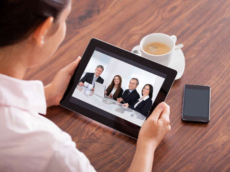 Photo pour Close-up Of Woman Looking At Video Conference On Digital Tablet - image libre de droit