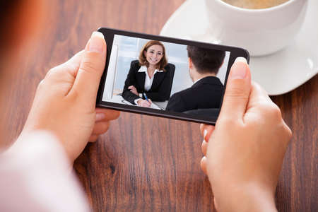 Photo pour Close-up Of Woman Looking At Video Conference On Mobile Phone - image libre de droit