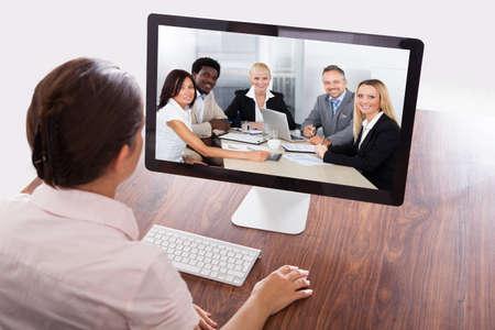 Photo pour Businesswoman Sitting At A Desk Watching An Online Presentation On The Computer - image libre de droit