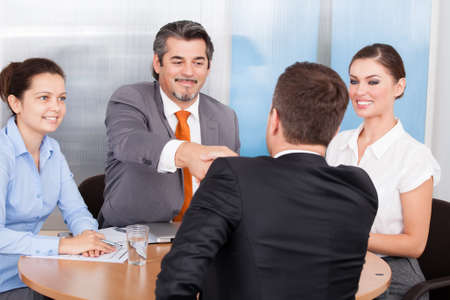 Two Business Partner Shaking Hands In Front Of Colleagues