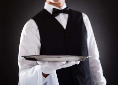 Portrait Of A Male Waiter Holding Tray Over Black Background